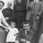 Mario, a year and a half old, with white smock, between mother and brother Toni, behind the grandparents.